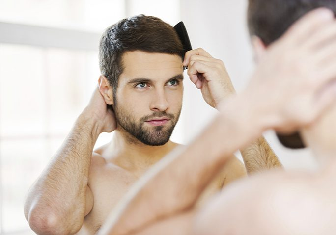 Morning routine. Rear view of handsome young beard man combing his hair while standing against a mirror